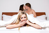 Cheeky young woman in a threesome or the cheating partner in an affair peeking out of the bottom of the bedclothes with a saucy expression as a young couple at the top of the bed share a loving kiss