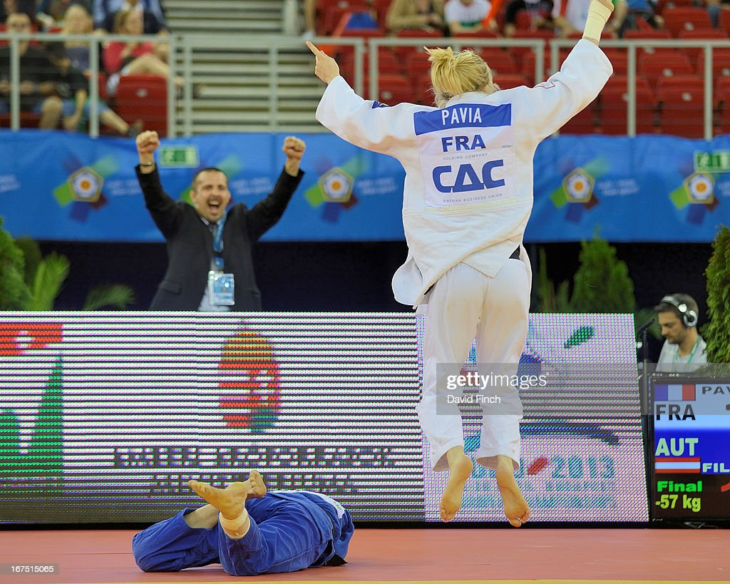 Cheered on by her coach, Automne Pavia of France celebrates winning the u57kgs final against Sabrina Filzmoser (blue) of Austria at the Budapest European Championships held at the Papp Laszlo Sports Hall, on April 25, 2013 in Budapest, Hungary. The event takes place from the 25-28.