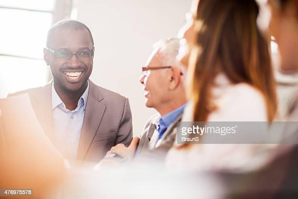 陽気なアフリカ系アメリカ人のビジネスマンお仕事仲間との会話を求めます。