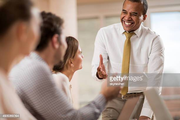 Cheerful African American businessman talking to his colleagues.