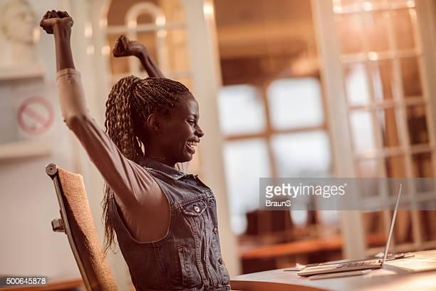 Fröhlich afroamerikanischen Geschäftsfrau feiert ihren Erfolg im Büro.