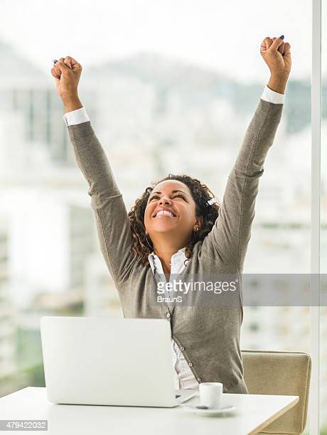 Cheerful African American businesswoman celebrating her business success.