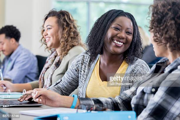 Cheerful African American college student smiles while talking with friend