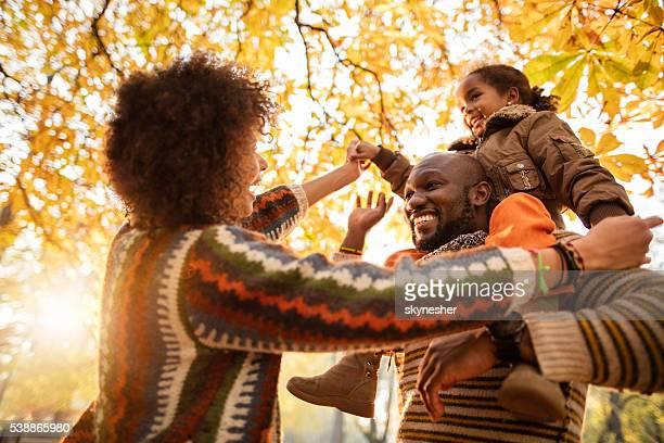 Fröhlich afroamerikanischen Familie Spaß haben im Herbst park.