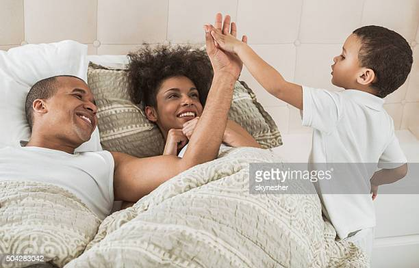 Cheerful African American family in bedroom.