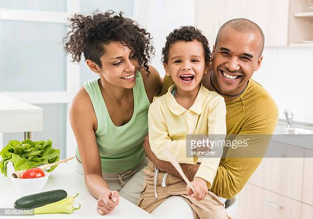 Cheerful African American family in the kitchen looking at camera.