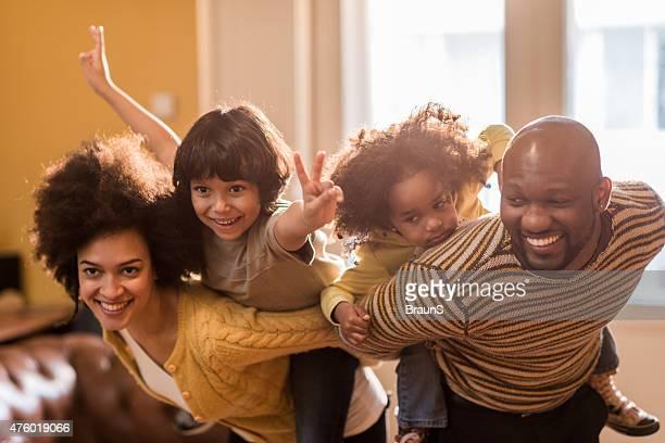 Alegre família afro-americana piggybacking em casa.