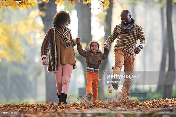 Cheerful African American family walking through leaves in autumn park.