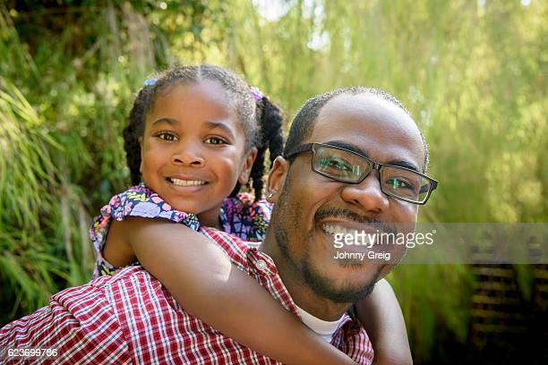 Cheerful African American father giving daughter piggy back