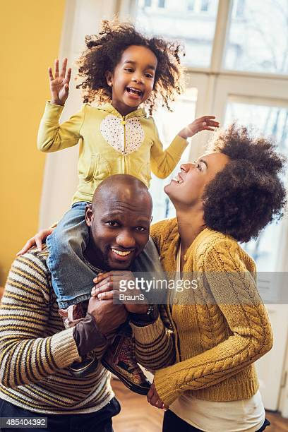 Cheerful African American parents having fun with their little daughter.