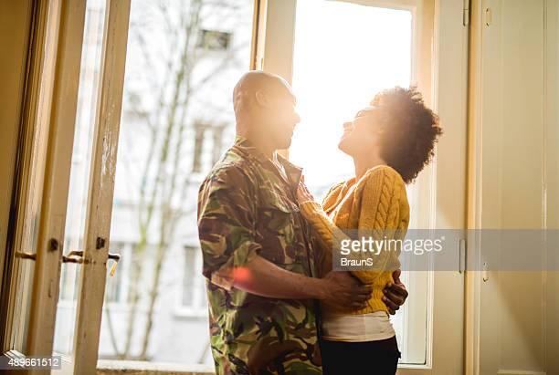 Joyeux soldat afro-américain à la maison à sa femme.
