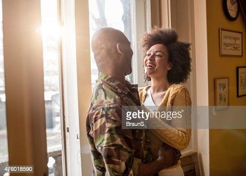 Alegre mulher afro-americana a falar com o marido militar.