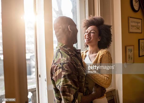 Gaie femme afro-américaine parler à son mari militaire.