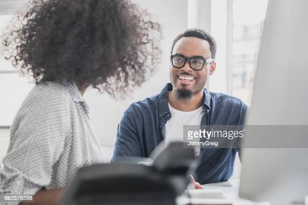 Cheerful African businessman in glasses with goatee listening to woman
