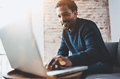 Cheerful African man using computer and smiling while sitting on the sofa.Concept of young business people working at home.Blurred background,flares