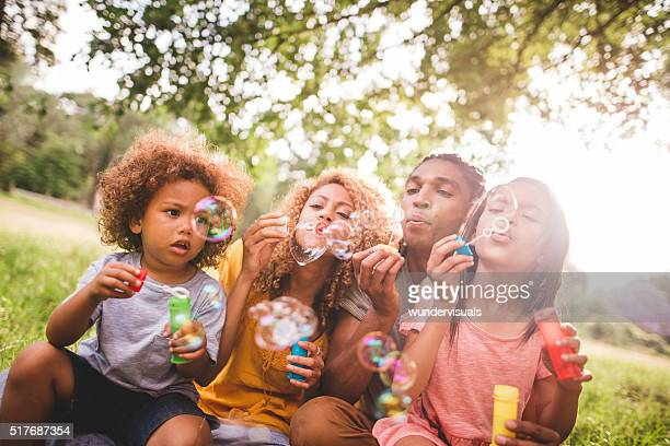 Cheerful african-american family bonding and blowing bubbles in