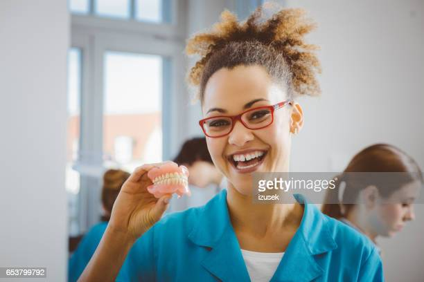 Cheerful afro american student holding denture