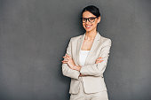 Cheerful young businesswoman in glasses keeping arms crossed and looking at camera with smile while standing against grey background