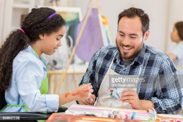 Cheerful art teacher helps young female student