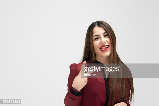 Cheerful attractive girl making victory sign while shpwing her t : Stock Photo