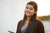 Cheerful attractive Indian young women using digital tablet at outdoor background.
