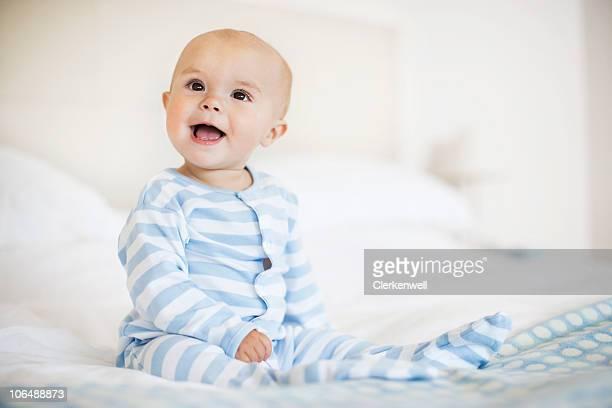 Joyeux petit garçon (6-11months) assis dans le lit, tandis que les looks de l'hôtel