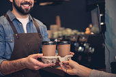Close up female hand taking cup of hot coffee from beaming unshaven worker in confectionary shop. Order concept