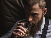 Portrait of attractive rich man enjoying alcohol drink. He is sitting and relaxing. The man is looking forward with confidence