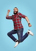 Smiling hipster man having fun and jumping in studio.
