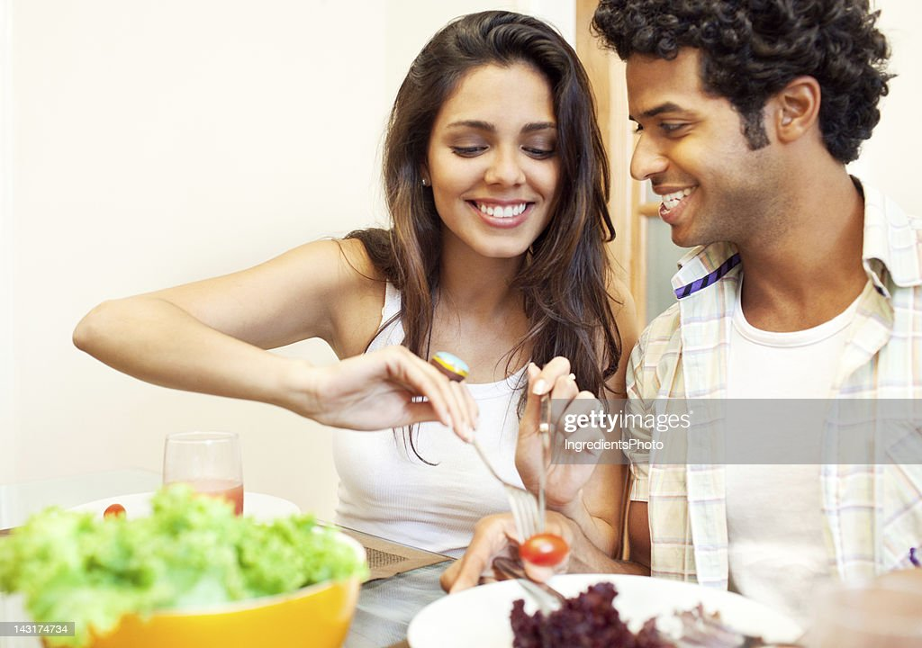 Cheerful beautiful brazilian couple having lunch at home. : Stock Photo