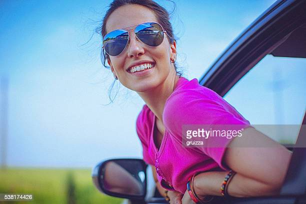 Cheerful, beautiful, young woman rests looking out the car window