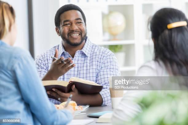 Cheerful Bible study teacher leads office Bible study