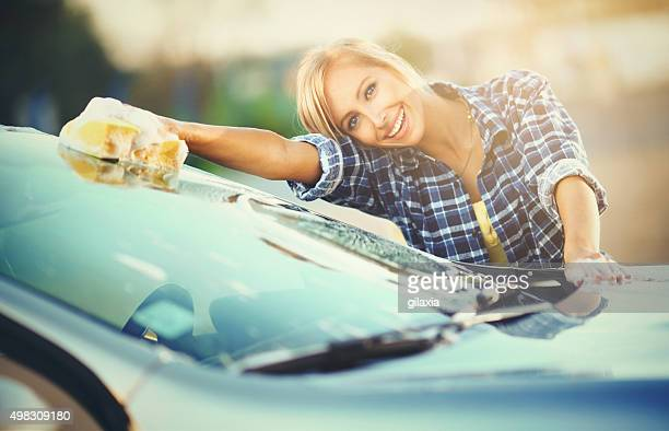 Cheerful blond woman washing her car.