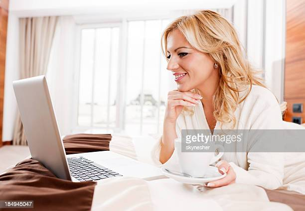 Cheerful blonde female using her laptop and drinking coffee.