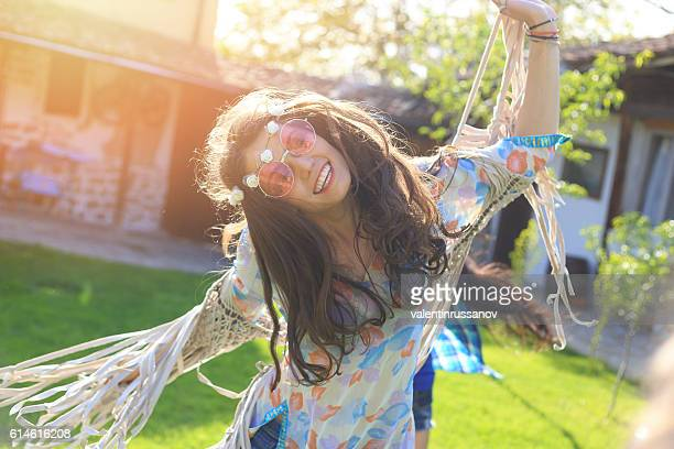 Cheerful boho woman dancing on grass
