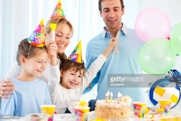 Cheerful boy celebrating birthday with sister and parents.