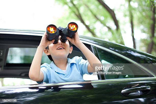 Cheerful boy leaning out of car window and looking with binoculars