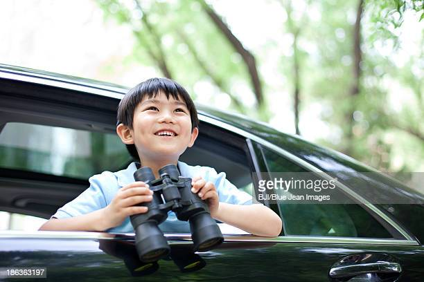 Cheerful boy leaning out of car window with binoculars in hands