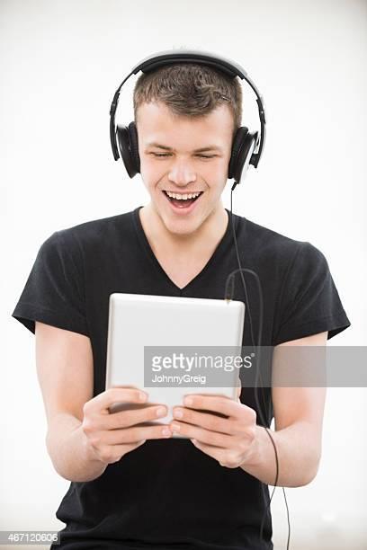 Cheerful Boy Listening Music Through Tablet