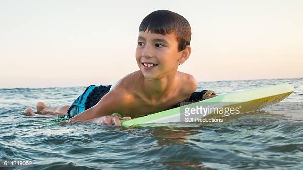 Cheerful boy uses body board in ocean