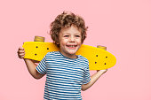 Little curly boy holding yellow longboard and looking away on pink background.