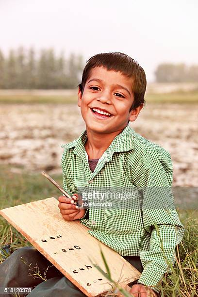 Cheerful boy writing & studying outdoor