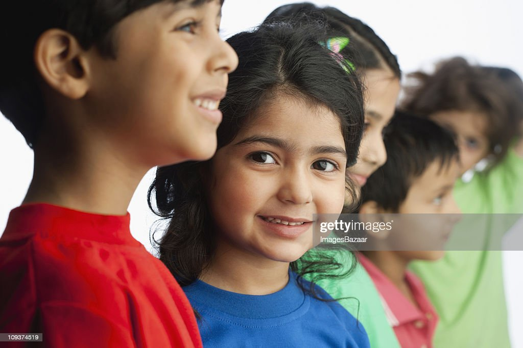 Cheerful boys (6-7) and girls (4-5) standing side by side : Stock Photo