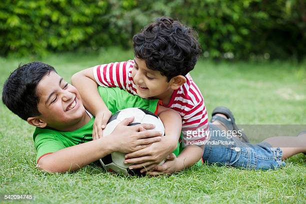 Cheerful brothers playing with soccer ball in park