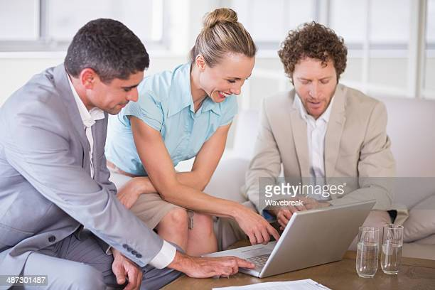 Cheerful business colleagues using laptop