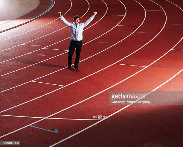 Cheerful business executive with hands raised on race track