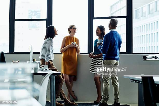 Cheerful business people standing by office window