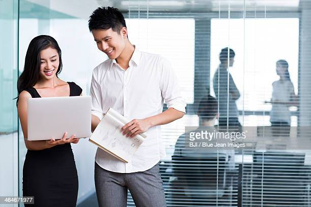 Cheerful business people using laptop