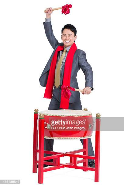 Cheerful businessman playing traditional Chinese red drum