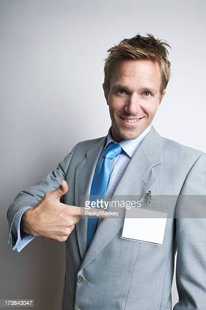 Cheerful Businessman Pointing to Name Tag